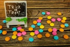 Halloween-Dekoration Süßes sonst gibt's Saures mit Süßigkeit auf hölzernem Hintergrund lizenzfreie stockfotografie