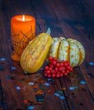 Halloween-Dekorationen, -brennende Kerze und -kürbise auf einem Holztisch stockfotos