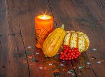 Halloween-Dekorationen, -brennende Kerze und -kürbise auf einem Holztisch Stockbilder