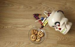 Halloween-Dekorationsschädel mit Bonbons ein d-Plätzchen in einer Platte Stockfotos