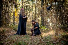 Halloween demon and witch in the woods stock photography
