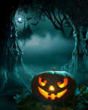 Halloween design. Glowing pumpkin in a dark scary forest church Stock Photos