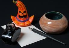 Halloween desktop. With orange pumpkin, pen, ink and paper Stock Photos