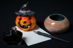 Halloween desktop. With orange pumpkin, pen, ink and paper Royalty Free Stock Photography