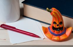 Halloween desktop. With orange pumpkin, red pen, blue book, white cup and paper Royalty Free Stock Image