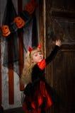 Halloween devil girl closing old wooden door. Cute halloween devil girl with blonde hair with horns in costume in red and black closing old wooden door indoors stock images