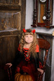 Halloween devil girl in costume in retro interior. Halloween devil girl in costume in red and black with horns sitting on pumpkin on chair in retro interior royalty free stock photo