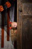 Halloween devil girl looking out of door. Blonde halloween devil girl with red horns looking out of old wooden door indoors royalty free stock image