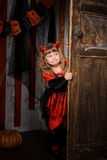 Halloween devil girl looking out of old door. Halloween devil girl in costume in black and red with horns looking out of old wooden door indoors royalty free stock photography
