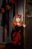 Halloween devil girl opening old door. Halloween devil girl in costume in red and black with horns opening old wooden door indoors royalty free stock photo