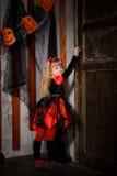 Halloween devil girl opening old wooden door. Cute halloween devil girl with blonde hair with horns in costume in red and black opening old wooden door indoors royalty free stock photo