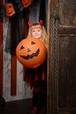 Halloween devil girl with pumpkin at door. Blonde halloween devil girl with red horns and smiling pumpkin at old wooden door indoors stock images