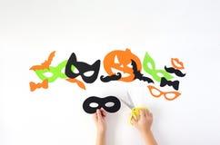 Halloween Die Papiermasken auf einem weißen Hintergrund, die vom Papier herausgeschnitten werden stockfoto