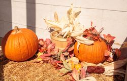 Halloween display of fall leaves and pumpkin on bails of hay stock photo