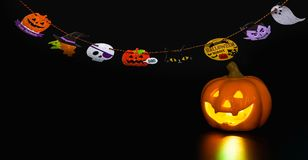 Halloween doll. Halloween pumpkin doll with light and flag for decoration on Halloween day on black background Royalty Free Stock Photo
