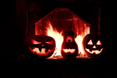 Halloween drei Kürbise am Kamin mit einem Feuer im dar Lizenzfreie Stockfotografie