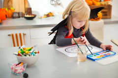 Halloween dressed girl drawing pumpkin Jack-O-Lantern Stock Images