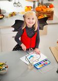 Halloween dressed girl drawing pumpkin Jack-O-Lantern on paper Royalty Free Stock Photo