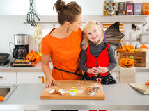 Halloween dressed girl with mother cutting out cookies Stock Images