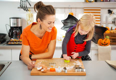 Halloween dressed girl with mother cutting out cookies Royalty Free Stock Photos