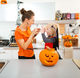Halloween dressed girl with young mother scaring each other. In kitchen decorated for horror party night. Traditional autumn holiday Stock Images