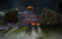 Halloween Drone. Halloween pumpkin installed on a drone flying over an old cemetery Stock Image