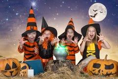 halloween Dzieci czarownicy i czarownicy gotuje napój miłosnego w kotle z banią i czary książką Zdjęcia Royalty Free