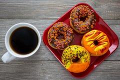 Halloween en de Herfst kleurden smakelijke kleurrijke die donuts voor ontbijt op een keukenlijst wordt gediend met kokend hete ko stock foto