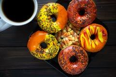 Halloween en de Herfst kleurden smakelijke kleurrijke die donuts voor ontbijt op een keukenlijst wordt gediend met kokend hete ko stock afbeelding