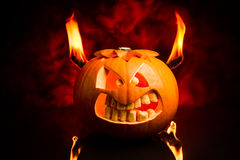 Halloween evil pumpkin with flames and red smoke in the background. Evil face of Halloween pumpkin with flames and red smoke in the background Royalty Free Stock Photo