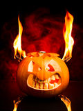 Halloween evil pumpkin with flames and red smoke in the background. Evil face of Halloween pumpkin with flames and red smoke in the background Royalty Free Stock Photos