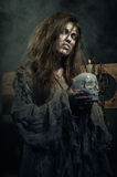 Halloween. The evil witch with a skull in his hands. Halloween. The Middle Ages. The evil witch with a skull in his hands royalty free stock photo