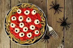 Halloween eyeball pasta, above view on old wood with spiders Royalty Free Stock Photography