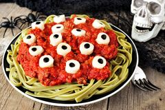 Halloween eyeball pasta scene with decor on aged wood Royalty Free Stock Images