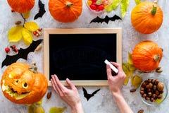 halloween förbereda sig Head near pumpor för pumpa och svart skrivbord för anmärkningar på grå modell för bästa sikt för bakgrund Arkivfoto