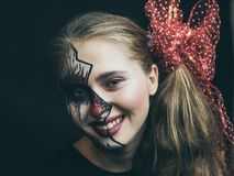 Halloween, the face of a girl is a doll, the floor of a face is dead. A woman with a horrible make-up. stock images