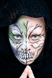 Halloween Face Painting. Young woman who looks dangerous and crazy with Halloween face painting Stock Image