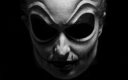 Halloween face. Woman with face painting in dark room Royalty Free Stock Image