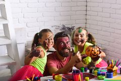 Halloween family with colorful paint. Halloween children with happy face in paint. Holiday and party celebration. Kids or small girls with bearded men father royalty free stock photography