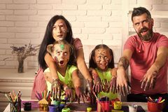 Halloween family with zombie hands in paints. Girls, mother, father with scary colored faces. Body art and painting. Creativity and imagination concept stock photography