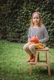 Halloween feliz Assentos de sorriso bonitos da criança na cadeira e em posses de madeira pouca abóbora Jack OLanterns fora imagens de stock royalty free