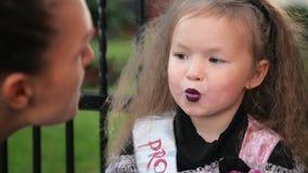 Halloween feliz A jovem mulher atrativa com sua filha bonito pequena est? preparando-se a Dia das Bruxas fora Mam? com filme
