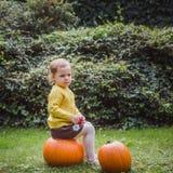 Halloween feliz A menina bonito está sentando-se em uma abóbora e está guardando-se uma maçã em sua mão imagem de stock