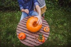 Halloween feliz Pai e filha que cinzelam a abóbora para Dia das Bruxas fora da opinião de ângulo alto, mãos Família feliz imagem de stock royalty free