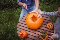 Halloween feliz Pai e filha que cinzelam a abóbora para Dia das Bruxas fora da opinião de ângulo alto, mãos Família feliz imagens de stock royalty free