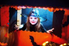 Halloween feliz Uma menina bonita pequena em um traje da bruxa comemora com abóboras fotografia de stock royalty free