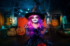 Halloween feliz Uma menina bonita pequena em um traje da bruxa comemora com abóboras fotos de stock royalty free