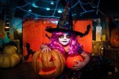 Halloween feliz Uma menina bonita pequena em um traje da bruxa comemora com abóboras imagens de stock royalty free