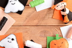 Halloween felt craft embellishments. Mixed Halloween ornaments, colored felt sheets on wooden table with copy space for text. Hand made witch with broom, pumpkin Royalty Free Stock Photo