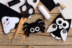 Halloween felt decorations. Felt ghost, spider, owl decorations on a vintage wooden table. Sewing tools and materials. Things to make with felt sheets. DIY felt stock photos